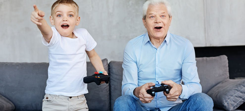 An older man and a child playing video games. An example of what older gamers look like.